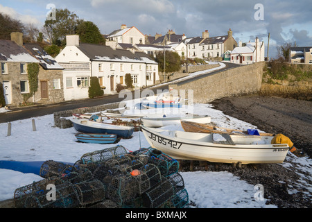 Moelfre Isle of Anglesey North Wales UK December Lobster pots and boats on snow covered beach of  small fishing - Stock Photo