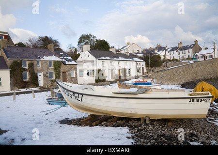 Moelfre Isle of Anglesey North Wales UK December Motor boats on snow covered beach of this small fishing village - Stock Photo