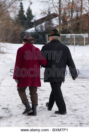 Elderly German couple walking along a rural  snow covered path Bavaria Germany - Stock Photo