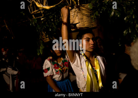 Young women dressed with traditional regional clothing carry baskets in their heads during holy week celebration, - Stock Photo