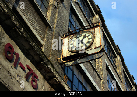 Broken clock on the side of an old factory in East London - Stock Photo