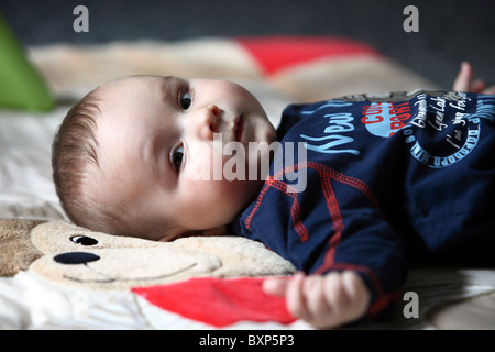 6 month old little boy laying in his children room, on a blanket, smiling, looking happy and friendly. - Stock Photo