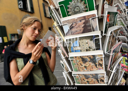young woman looking at postcards on a shop stall in Cortona, Tuscany, Italy - Stock Photo
