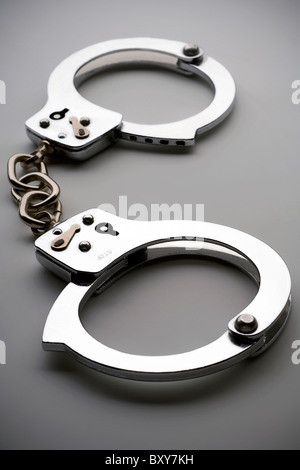 closed handcuffs on gray surface - Stock Photo