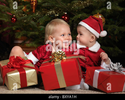 Two year old girl and an eight month old boy sharing gifts under a Christmas tree - Stock Photo