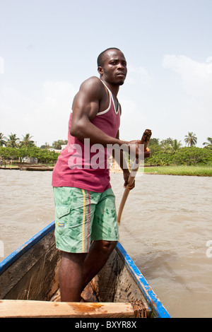 A man oars across Lac Togo on the way from Togoville in a traditional canoe. - Stock Photo