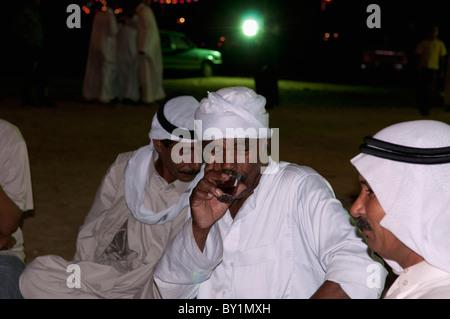 Guests converse over tea during traditional Bedouin wedding celebration. El Tur, Sinai Peninsula, Egypt - Stock Photo
