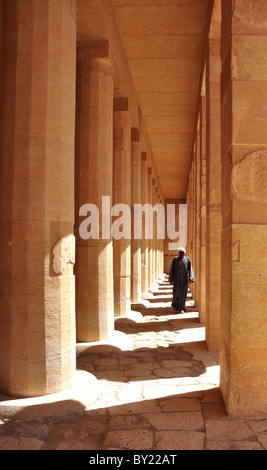 Man walking through pillars in the Hatshepsut Temple near Luxor, Egypt. - Stock Photo
