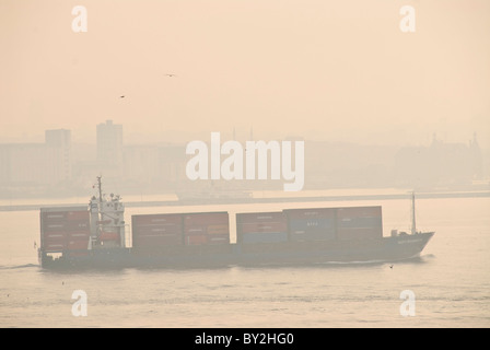 A large cargo ship passes through the narrow intersection of the Sea of Marmara, the Golden Horn, and the Bosphorus - Stock Photo