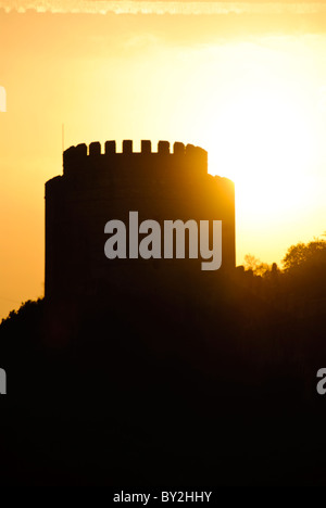 Silhouette against the setting sun of the Rumelian Castle (Rumelihisari), a 15th century fortress on the banks of - Stock Photo