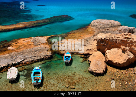 Milos island, Greece. A small natural 'harbor' very close to Fyriplaka beach with fishing boats and crystal clear - Stock Photo
