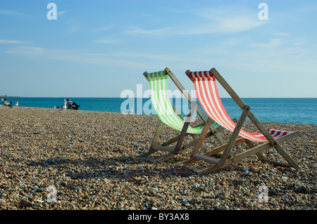 Two wooden deckchairs on a beach in Brighton, East Sussex, England. - Stock Photo