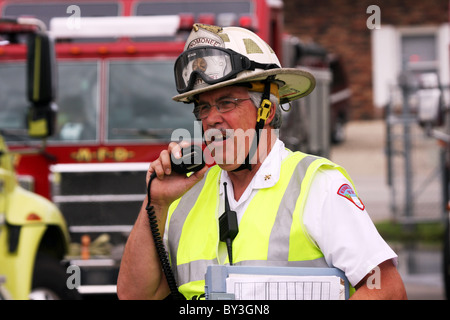 A firefighter talking on the radio emergency scene - Stock Photo