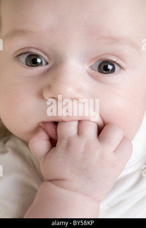 A baby sucking on his fingers - Stock Photo