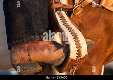 A cowboy boot in a horse stirrup, detail - Stock Photo