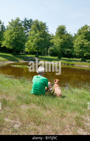 Man sitting with his dog near the water - Stock Photo