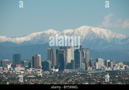 Downtown Los Angeles skyline and snow capped San Gabriel Mountains Southern California USA - Stock Photo