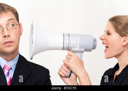 Close-up of young furious woman screaming at her boss through megaphone - Stock Photo