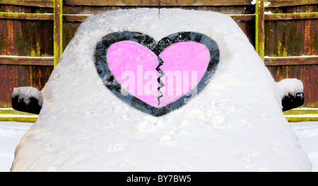 snow covered car with pink broken heart marked in the snow covered windscreen - Stock Photo