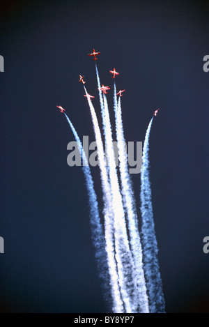 Canadian Forces Snowbirds flying in Close Formation at Air Show, performing Aerobatic Maneuver in Sky with Smoke - Stock Photo