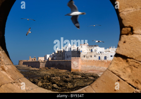 North bastion and ramparts of Essaouira Morocco viewed from Sqala du Port keyhole window with blue sky - Stock Photo