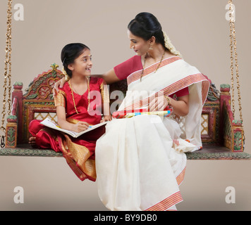 South Indian woman sitting with her daughter - Stock Photo