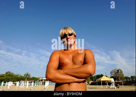 A tanned Italian lifeguard at the beach at Lake Trasimeno ,Campo del Sole, Tuoro, Umbria, Italy - Stock Photo