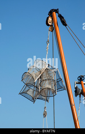 Lobster traps / creels hanging from mast, Breskens, The Netherlands - Stock Photo
