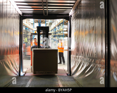 Workers loading truck with forklift - Stock Photo