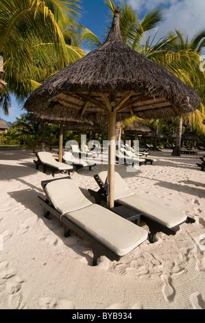 Sunbeds under sunshade on the beach of Le Paradis Hotel, Mauritius, Africa - Stock Photo