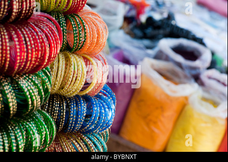 Indian glass bangles on a market stall in front of bags of coloured powder. Andhra Pradesh, India - Stock Photo