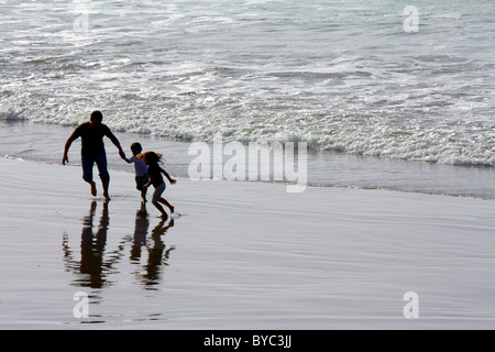 Father and two preschool children -- a boy and a girl -- running, playing, and laughing in the lake / ocean surf - Stock Photo