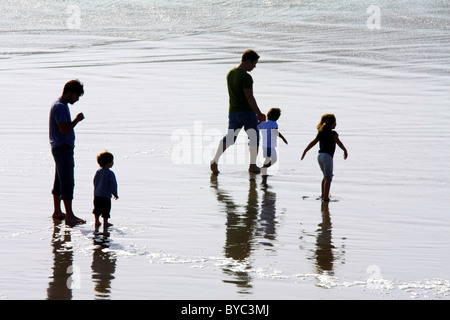 Two fathers and three preschool children walking, playing, and laughing in the Pacific Ocean surf at low tide; Oregon, - Stock Photo