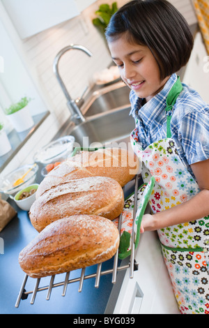 Girl holding metal grate with hot bread loafs - Stock Photo