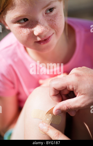 Father sticking adhesive bandage on his daughters knee - Stock Photo