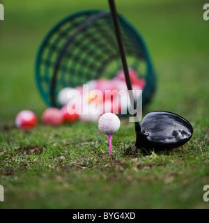 Golf ball on tee beside golf club - Stock Photo
