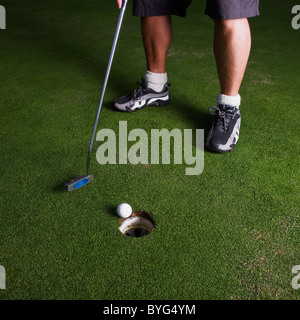 Male golfer on putting green - Stock Photo