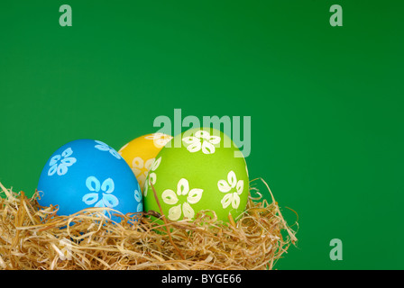 Easter painted eggs in the nest over green background - Stock Photo