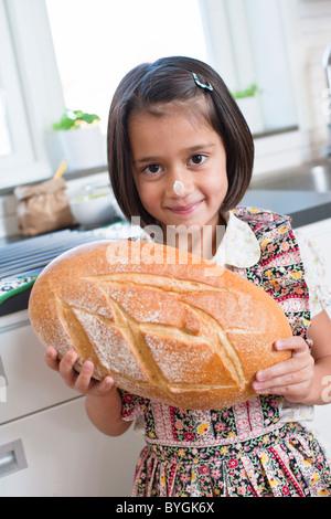 Portrait of girl holding freshly mad bread - Stock Photo