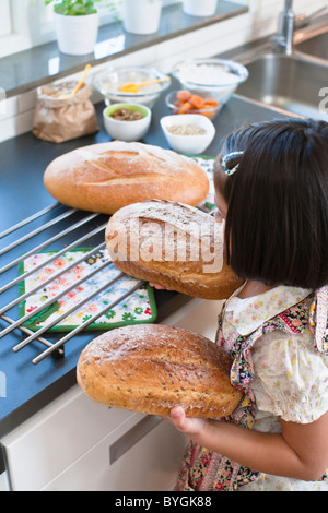Girl holding freshly made bread, high angle view - Stock Photo