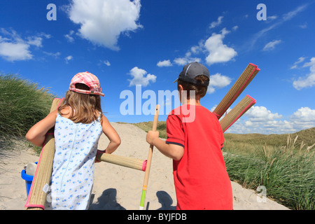 A girl and a boy on the way to the beach - Stock Photo