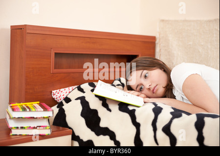 Tired female student is trying to read book - Stock Photo