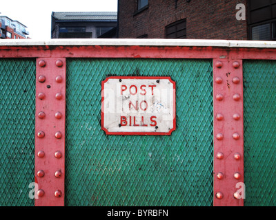 OLYMPUS DIGITAL CAMERA Sign on wall says post no bills in red and green painted setting on iron bridge. - Stock Photo