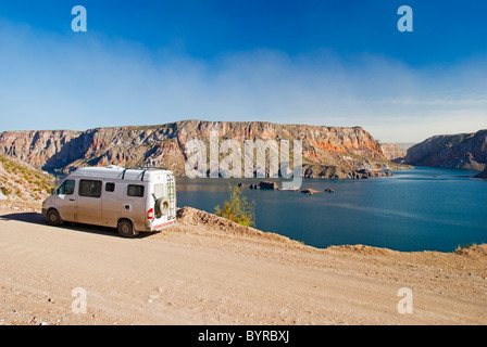 a camper van parked beside the lake in caòon del atuel; san rafael, mendoza, argentina - Stock Photo