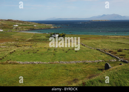 green fields and stone walls on inishbofin island off the coast in connacht region; county galway, ireland - Stock Photo