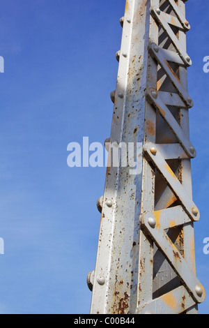 Vertical painted and rusted steel bridge beam against blue sky - Stock Photo
