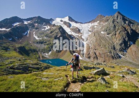 A hiker stands in front of the Grausee, Wilder Freiger glacier, and Cima Libera on the Stubai Hohenweg in Tyrol, - Stock Photo