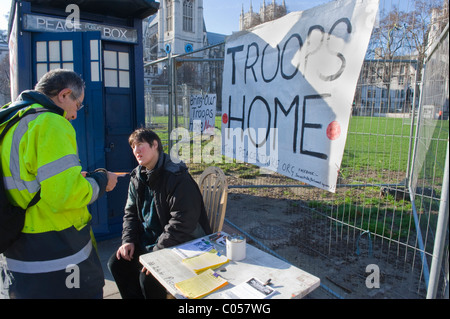 London , Westminster , Parliament Square peace camp with elderly protester chatting to fellow campaigner by posters - Stock Photo