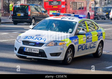 London , Westminster ,  emergency service police car Ford Mondeo with lights flashing speeds past Big Ben or  St - Stock Photo