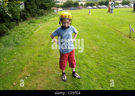 Young boy wearing a protective helmet used in the Irish national sport of Hurling in County Wexford, Ireland. - Stock Photo